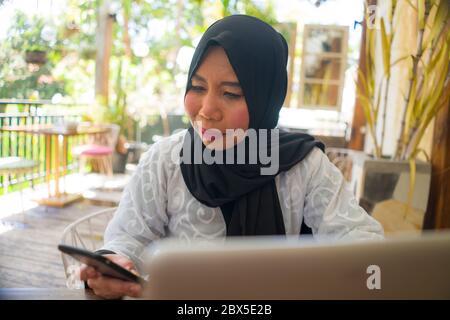 estilo de vida retrato de la mujer musulmana asiática de mediana edad Indonesia en la bufanda tradicional de la cabeza de Hijab trabajando relajado en el jardín casero que funciona negocio en línea Foto de stock
