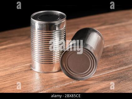 Dos largos enlatados de color plata sobre mesa de madera con fondo negro de primer plano
