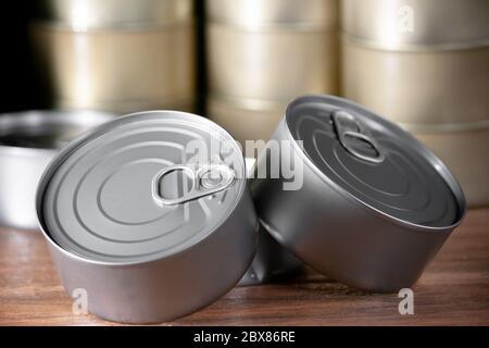 latas de atún de color plata en una vista de cerca y de fondo con muchas latas de atún en madera marrón