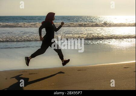 Joven mujer musulmana, sana y activa, en el Islam, hijab bufanda de cabeza corriendo y trotando en la playa usando ropa deportiva árabe tradicional en el fitn Foto de stock