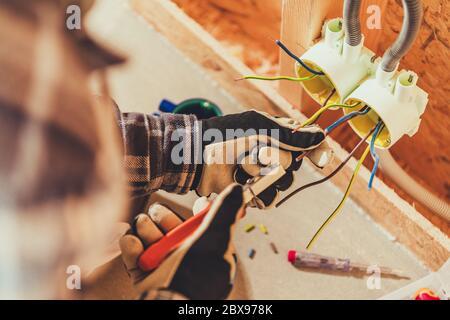 Instalación de tomas eléctricas dentro del edificio residencial Cerrar. Electricista profesional en el trabajo. Foto de stock