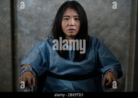 Joven loco y mentalmente loco mujer asiática contenida en silla de ruedas en el hospital mental que sufre de trastorno psiquiátrico como esquizofrenia mirando catato
