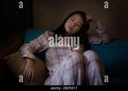 Retrato dramático oscuro de joven hermosa triste y deprimida mujer China asiática en pijama en casa sentado en el sofá de la sala de estar sintiéndose infeliz y co