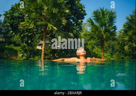 Retrato natural de estilo de vida de una mujer asiática de mediana edad, atractiva y feliz, relajada en un complejo tropical con piscina infinita con fondo de selva