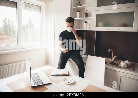 Joven programador caucásico está teniendo un descanso bebiendo un café y charlando por teléfono en la cocina