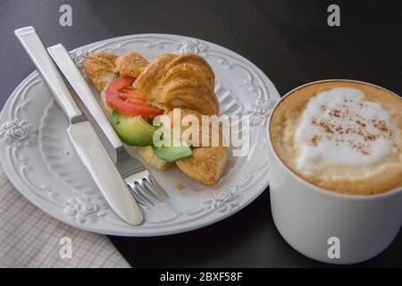 Croissant fresco relleno de aguacate y tomate, una taza de capuchino en una mesa oscura, luz de la mañana desde la ventana