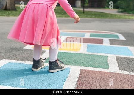 Niña con un vestido rosa jugando al hopscotch en el patio de recreo al aire libre, actividades al aire libre para niños