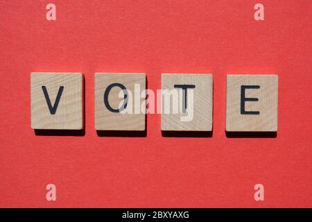 Votar, palabra en letras del alfabeto de madera 3d aisladas sobre fondo rojo