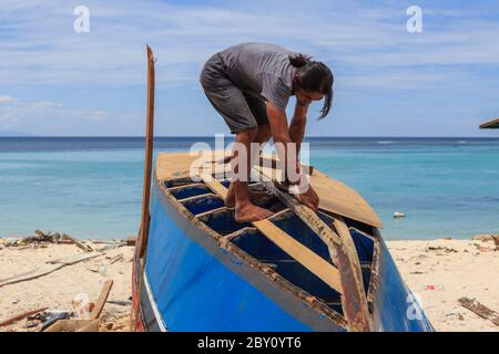 Isla Mantanani, Sabah, Malasia-CIRCA SEPTIEMBRE, 2017:el hombre no identificado está trabajando duro reparando el barco de madera en la isla de Mantanani, Kota Belud, Sab