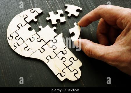 Una mano recoge un rompecabezas en forma de una bombilla como símbolo de una nueva idea, creatividad y puesta en marcha.