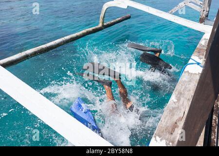 Los buceadores que hacen atrás se voltean al mar azul transparente desde el tablero de un barco. Hay varias maneras de bajar del barco cuando se bucea. Uno de ellos ya está