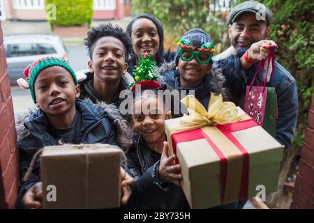 Retrato feliz familia llegando con regalos de Navidad en la puerta principal