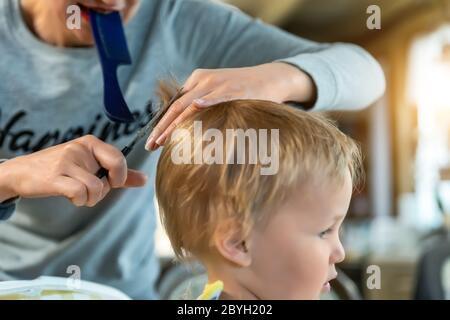 Primer plano joven adulto madre caucásica haciendo corte de pelo fot lindo adorable hijo niño en casa debido a cuarentena y cierre. Mamá cortando el pelo del niño