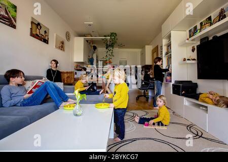 Muchos niños, haciendo diferentes actividades en casa, leyendo libros, jugando con juguetes, comiendo, corriendo, escuchando música, saltando