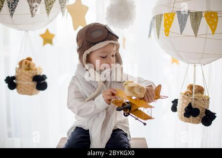 Niño pequeño lindo, chico, jugando con polluelos en casa, fingiendo que está volando en el cielo, piloto con avión y polluelo de mascota