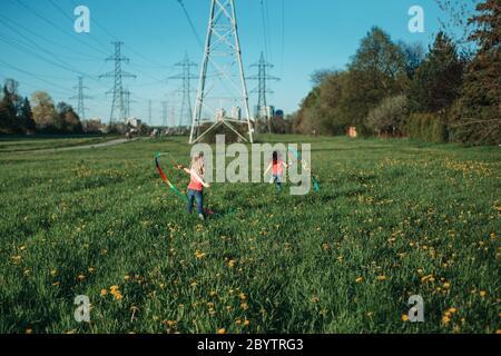 Niños felices niñas jugando con cintas en el parque. Unos niños adorables corriendo en el prado jugando juntos. Actividades al aire libre en el patio trasero para los niños.