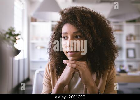 Retrato de una mujer de negocios de raza mixta pensando y sonriendo Foto de stock