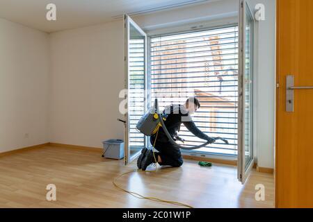 joven hombre profesional limpiador aspirando persianas sucias y limpieza a fondo