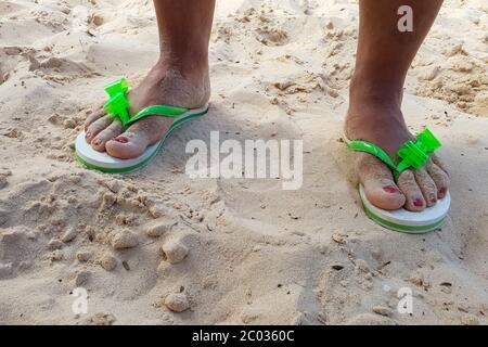 Pies femeninos en sandalias en una playa de arena