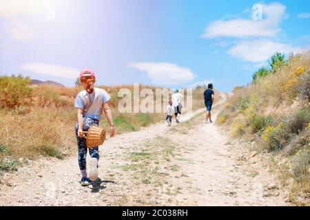 Familia con tres niños senderismo en el camino de la campiña a las montañas. Actividades en libertad con las familias. Una chica linda caminando por un camino
