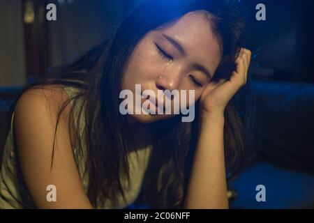 Joven hermosa mujer asiática triste y deprimida coreana llorando en lágrimas sobre la oscuridad en dolor sintiéndose preocupada y desamparado solando desesperada en el salón