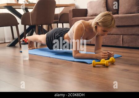 Mujer en forma de ajuste haciendo un ejercicio de la tabla del antebrazo Foto de stock
