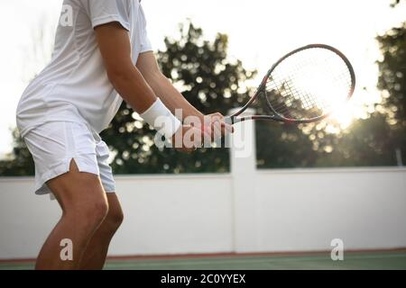 Entrenamiento de hombre caucásico en una cancha de tenis