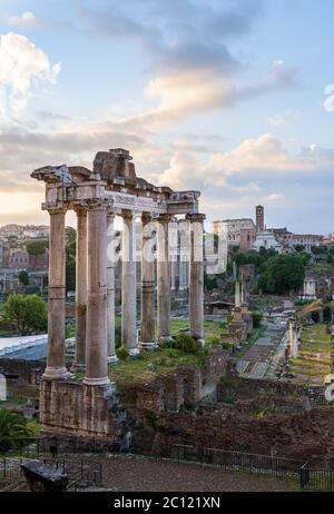 Columnas del antiguo Templo de Saturno al amanecer, en el Foro Romano, Roma, Italia, con ruinas de la Basílica Giulia, templos y el Coliseo Amphaith
