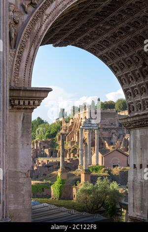 Las antiguas columnas en ruinas en el templo de Castor y Pollux aparecen a través de la puerta del Arco de Severo, un monumento en el Foro Romano, Roma, ITA