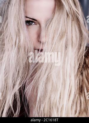 Chica con platino rubio cabello sucio sobre la cara