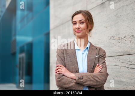 Mujer de negocios exitosa persona de negocios de pie brazos cruzados exterior de edificio corporativo de exterior elegancia agresiva confianza caucásica profesa Foto de stock