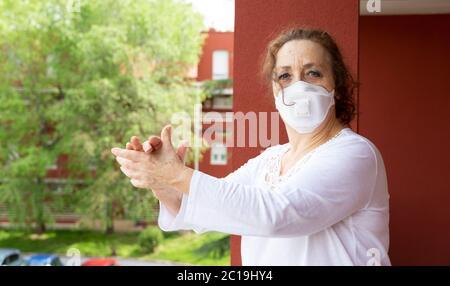 Retrato de una anciana con máscara médica aplaudiendo desde el balcón en agradecimiento a los trabajadores de la salud. Confinamiento por coronavirus. Covid-19 concept