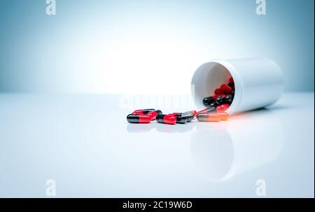Cápsulas de antibióticos rojo-negro las pastillas se extienden de la botella de plástico de la droga sobre fondo blanco. Industria farmacéutica. Resistencia a los antibióticos.