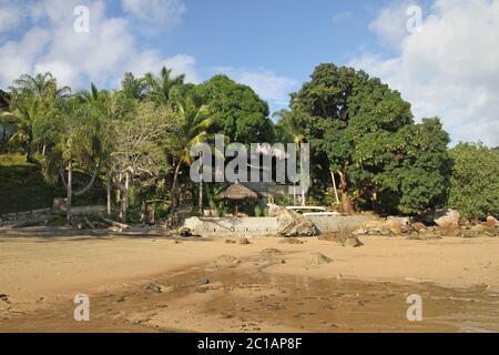 Vista de la lapa con techo de hojas de palma y los árboles en 293 en Komba Guest House desde la playa, Ampangorinana Village, Nosy Komba Island, Madagascar.