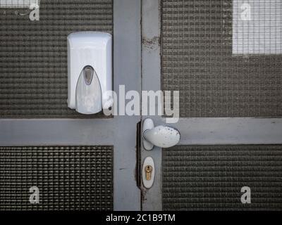 Dispensador de desinfectante de manos montado en la pared de la puerta de entrada con una cerradura y un pomo, en lugar público, un edificio residencial, distribuyendo alcohol hidroico