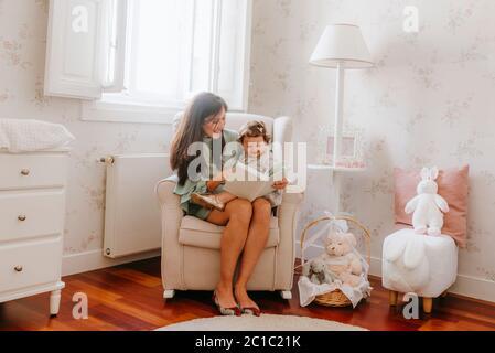 niña que se divierte sentada sobre su madre embarazada en la habitación