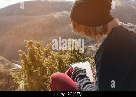 Retrato de una hipo chica con gafas de sol y un sombrero sentado en una roca al aire libre en las montañas contra un cielo azul. Independiente