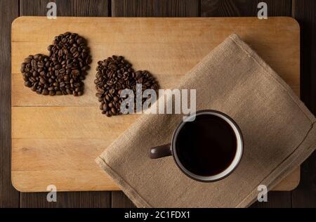 Un corazón de granos de café sobre un fondo de madera de color beige florecido con una taza de café. Concepto de amor, vacaciones, día de San Valentín, mujeres internacionales