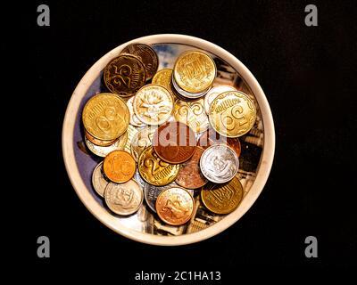 Pequeñas monedas de dinero en un plato sobre fondo negro.