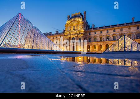 Museo del Louvre de París con reflexión nocturna en París, Francia