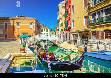 Paisaje urbano de Venecia con góndola y lanchas a motor amarradas en el estrecho canal de agua Río dei Frari, edificios coloridos y puente de piedra, región del Véneto, norte de Italia, fondo azul cielo en el día de verano