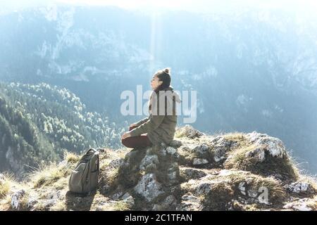 Una chica en soledad se sienta en la cima de una montaña con los ojos cerrados y medita, o está en busca de un alma o conciencia. La luz del sol cae directamente sobre ella. Cuidado de la salud mental