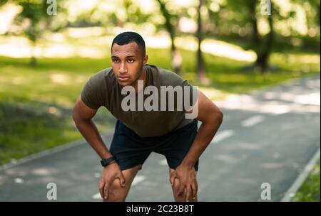 Joven corredor afroamericano tomando descanso después de su entrenamiento en el parque