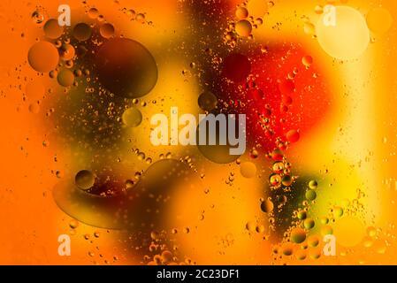 Imagen de estudio interior de luz abstracta y colores capturados sobre gotas de aceite en el agua, sobre un fondo colorido Foto de stock