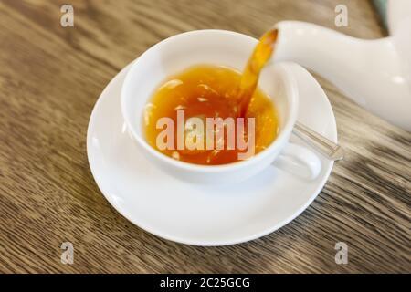 vierta el té fresco en una taza blanca Foto de stock