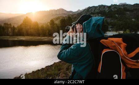 Hombre mayor en un viaje de senderismo tomando fotografías de la vista con una cámara digital. Hombre caminante junto al río en el bosque y haciendo fotos.