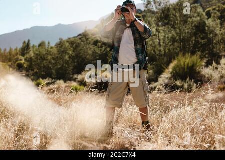 Hombre mayor en un viaje de senderismo haciendo fotos con una cámara digital. Hiker macho fotografiando una naturaleza.