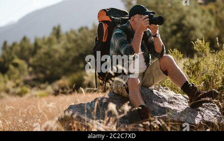 Hombre mayor fotografiando con una cámara digital. Hombre jubilado sentado en una roca y tomando fotos en un viaje de senderismo.
