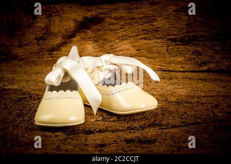 Pequeños zapatos de piel de patente recién nacido con arco sobre fondo de madera, armario de bautizo tradicional.