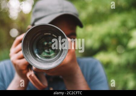 Primer plano retrato de un fotógrafo africano haciendo fotografías con una cámara digital